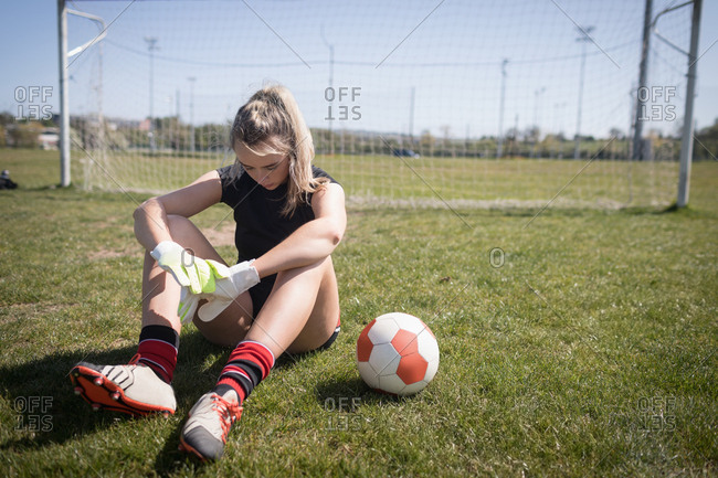 Full length of female soccer player resting on playing field during sunny day