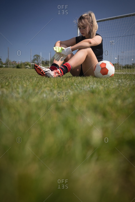 Full length of tired female soccer player sitting by goal post on field