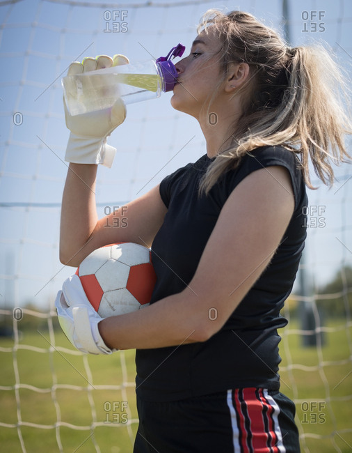 Thirsty young female soccer player drinking water while holding ball