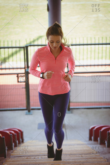 Young female athlete moving up on steps at track and field stadium
