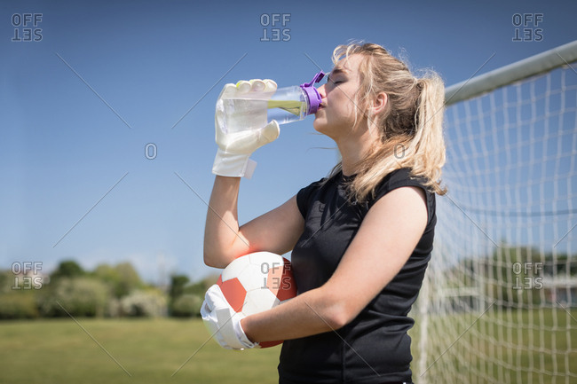 Thirsty female soccer player drinking water on field during sunny day