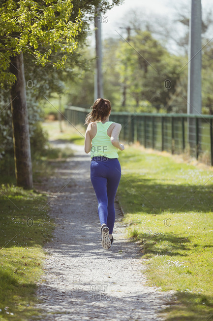 Rear view full length of female athlete running on pathway