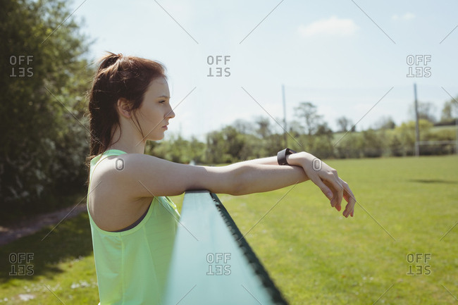 Thoughtful female athlete looking away while standing by railing on sunny day