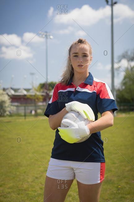 Portrait of female goalie with soccer ball standing on field against sky