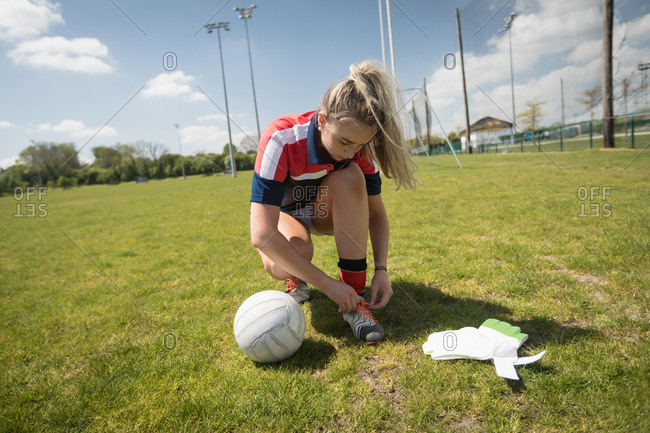 Full length of young female goalie tying shoelace on field