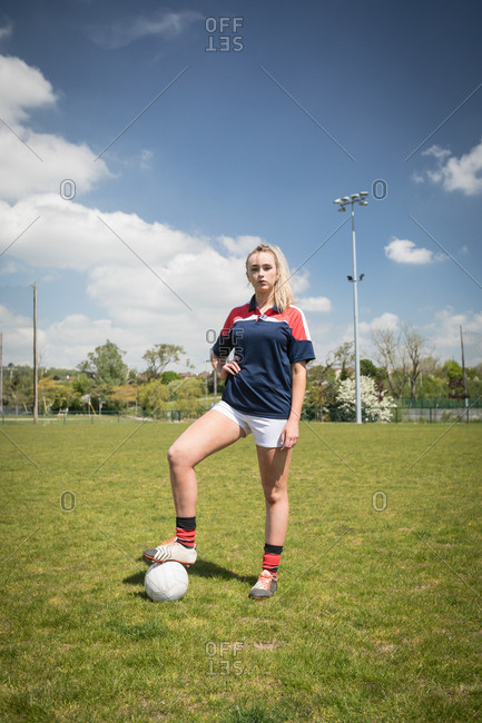 Full length of female soccer player with ball standing on field against sky