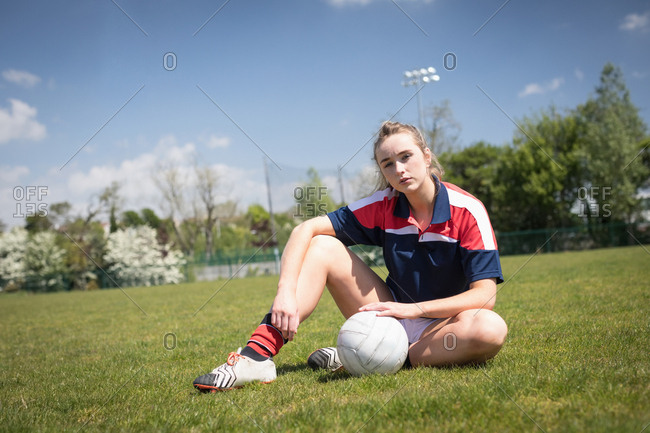 Portrait of young woman with soccer ball sitting on field against sky