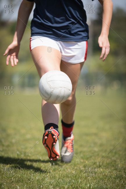 Low section of female player playing with soccer ball on field