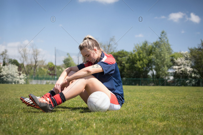 Tired soccer player with ball sitting on field during sunny day