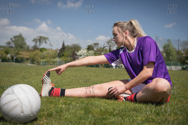 Full length of female soccer player by ball stretching on field