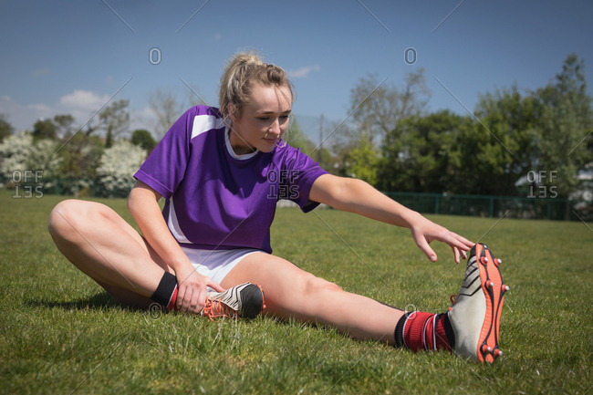 Full length of female soccer player exercising on field during sunny day