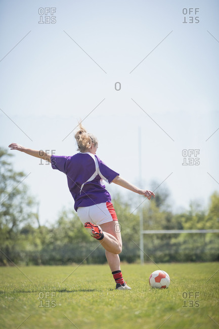 Rear view of woman kicking soccer ball on field against clear sky