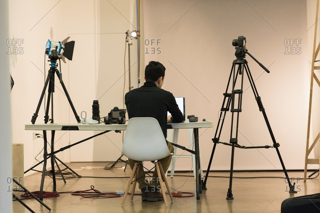 Rear view of photographer working while sitting on chair at studio