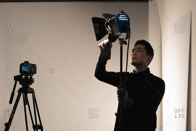 Concentrated male photographer adjusting light in studio