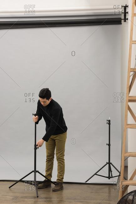 Photographer adjusting tripod against backdrop at studio