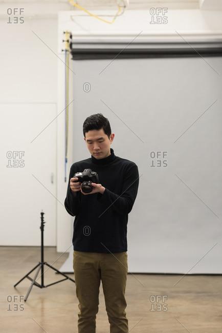 Man adjusting camera against backdrop at studio