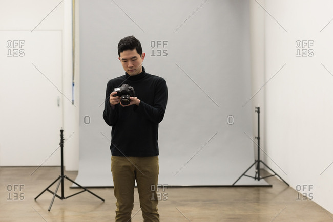 Male photographer adjusting camera against backdrop at studio
