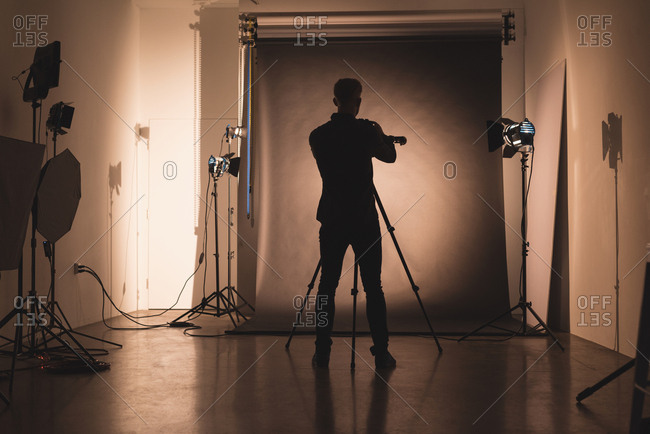 Rear view of male photographer adjusting camera against backdrop at studio