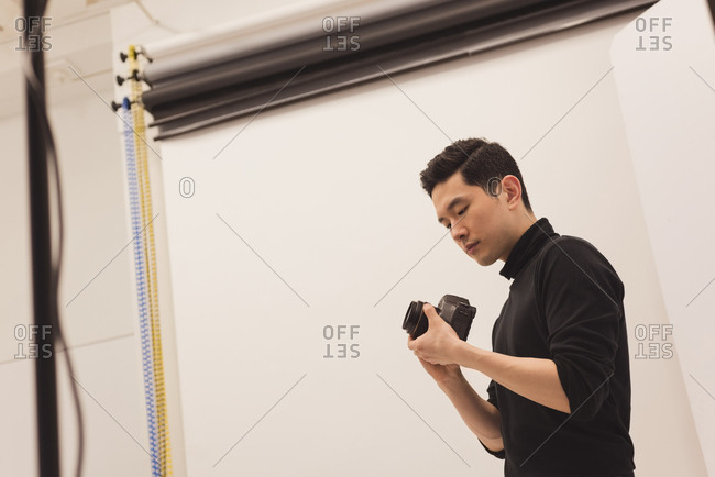 Photographer adjusting camera at studio