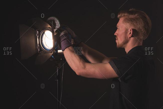 Side view of male photographer adjusting strobe light at film studio