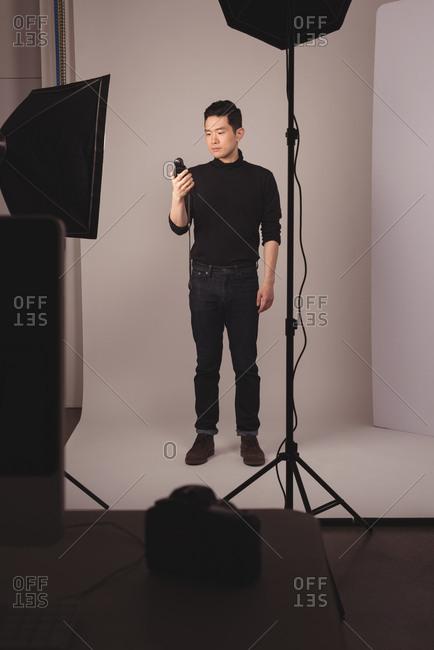 Full length of photographer holding camera flash against backdrop at studio