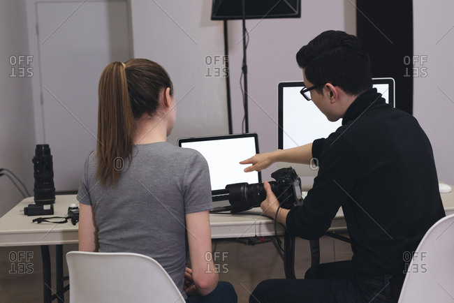 Male photographer explaining assistant while using laptop at studio