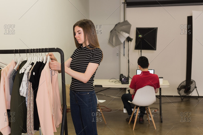 Young model choosing clothes on rack with photographer sitting on chair at studio