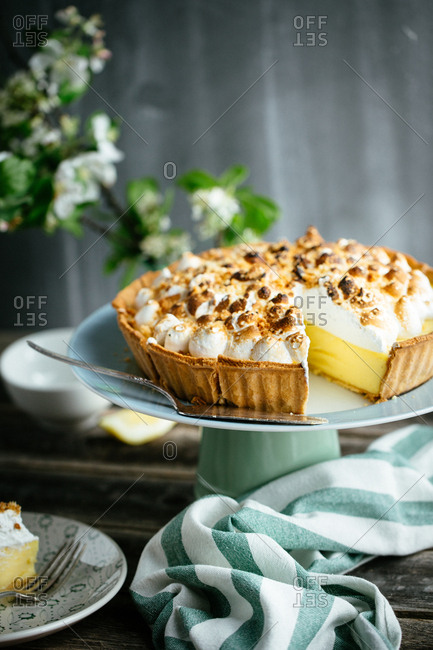 Lemon meringue pie on a cake stand with slice missing