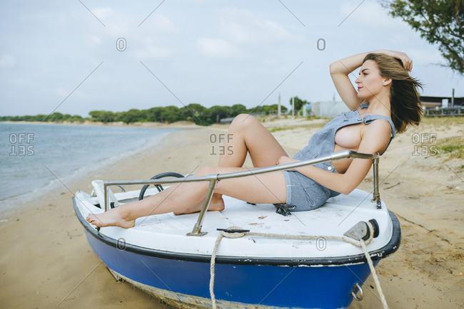 Young woman in overall shorts on a beached boat
