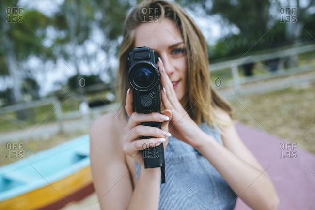 Young woman using vintage video camera on a  beach