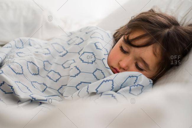 Girl slumbering under a blanket