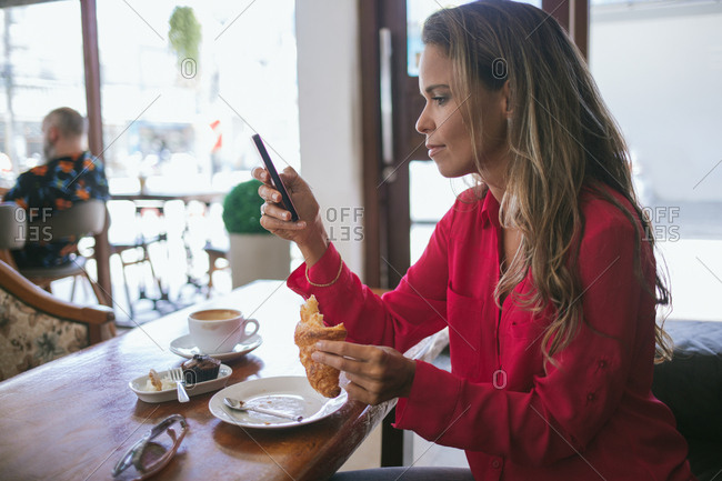 Woman holding croissant using phone