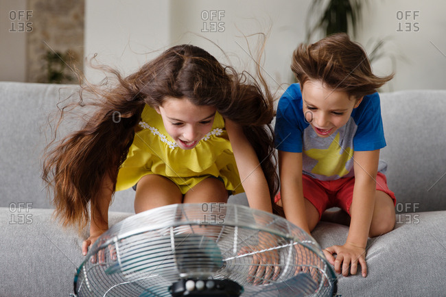 Two kids on couch playing with fan