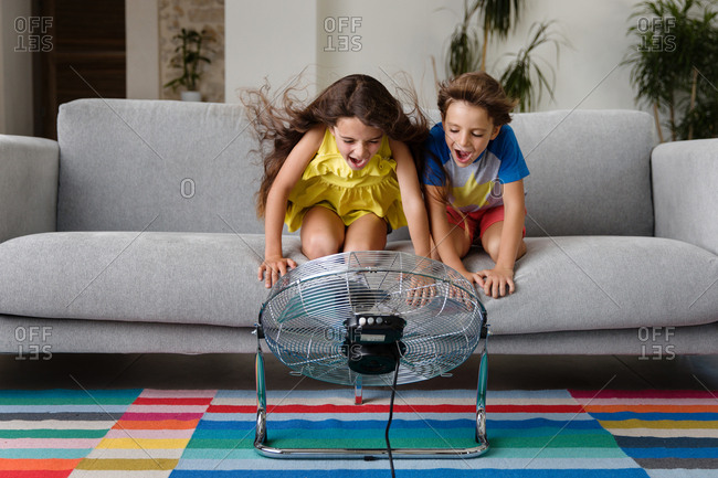Kids on couch playing with fan