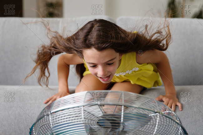 Girl playing in fan on couch