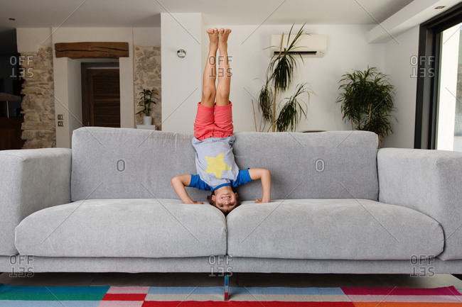 Boy doing headstand on couch