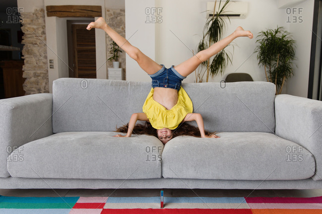 Girl doing headstand on couch