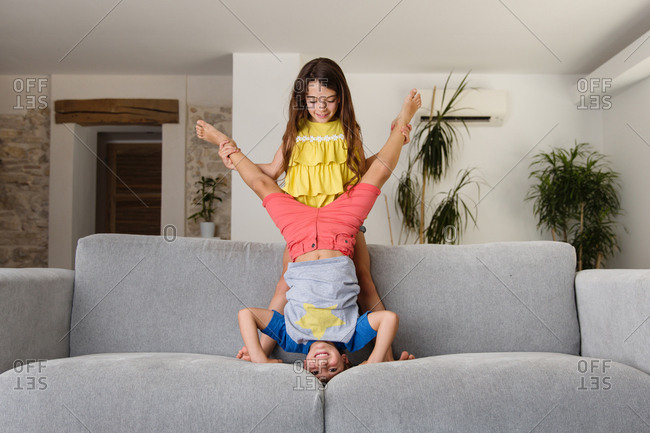 Girl helping boy with headstand