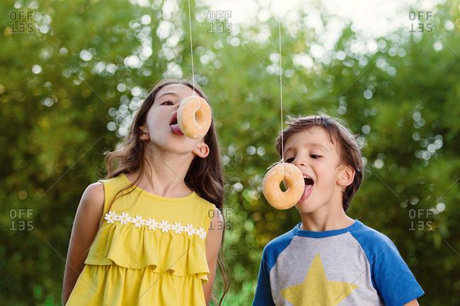 Kids eating donuts on strings