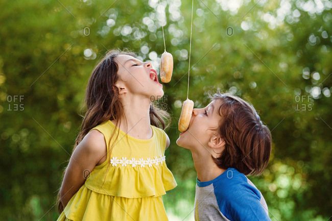 Boy and girl eating doughnuts on strings