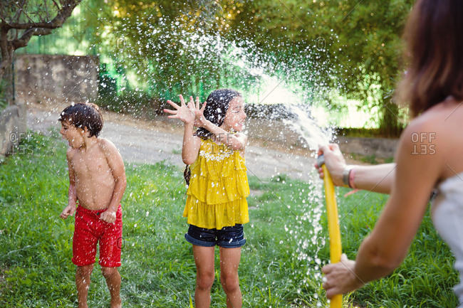Mom spraying kids with hose