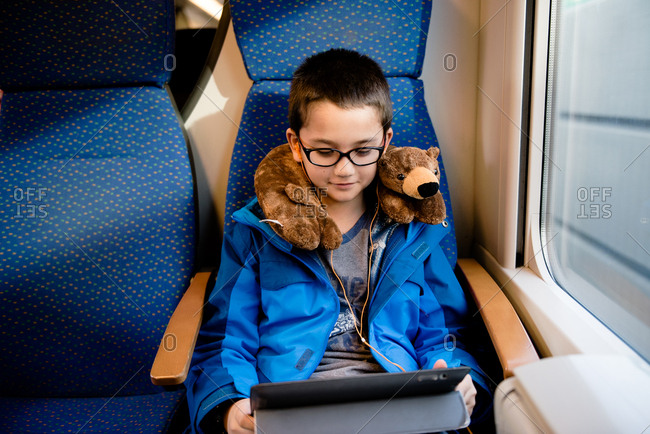 Boy using device riding  a train