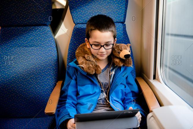 Boy using device riding  a train