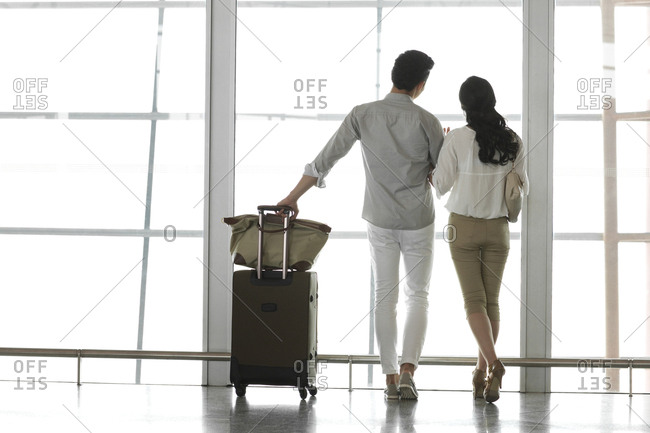 Young couple at the airport looking at view