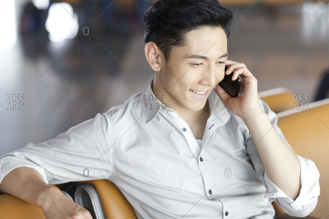 Young man talking on the phone in airport lounge