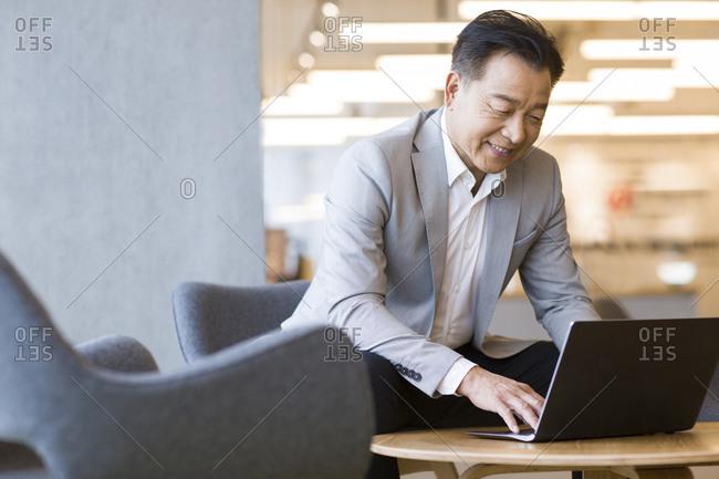 Confident businessman using laptop