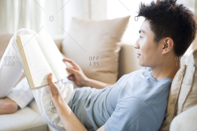 Young man reading a book on the sofa