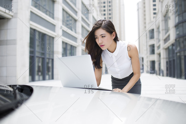 Confident businesswoman using laptop on car