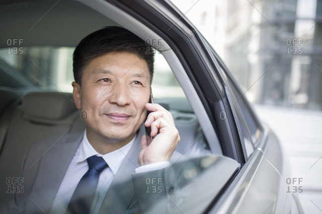 Confident businessman talking on cell phone inside car