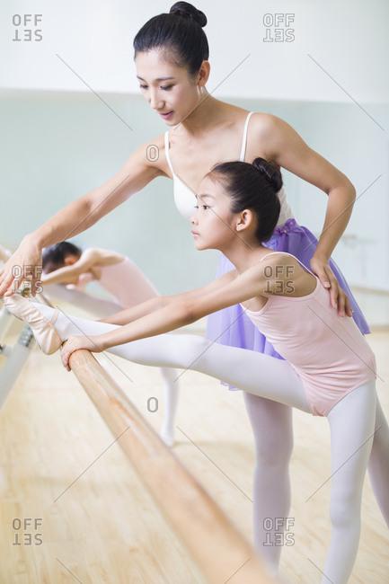 Young ballet instructor teaching girl in ballet studio